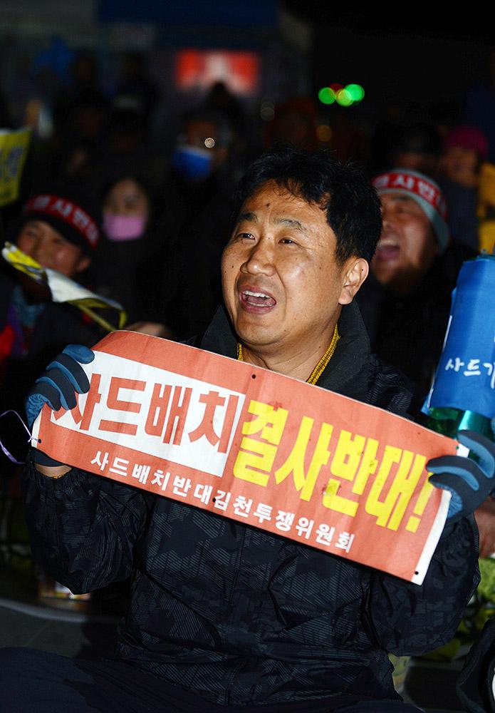 """3月15日,在韩国庆尚北道金泉市,民众手持反""""萨德""""标语参加烛光集会。"""