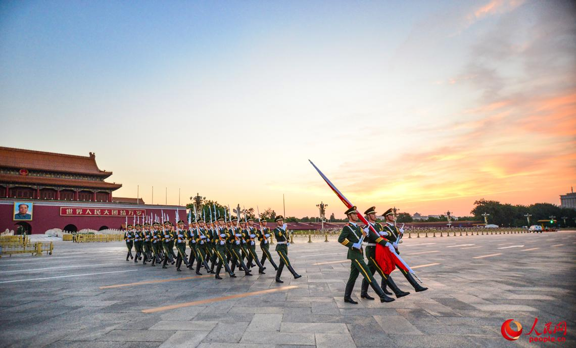 7月11日清晨4时许,国旗护卫队伴着朝霞,迈着整齐的步伐进入广场举行升国旗仪式。 安晓惠摄