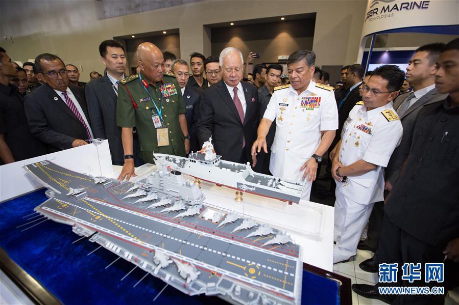 """4月16日,在马来西亚吉隆坡举行的第16届马来西亚亚洲防务展上,马来西亚总理纳吉布(中)在""""中国防务""""展区参观。"""