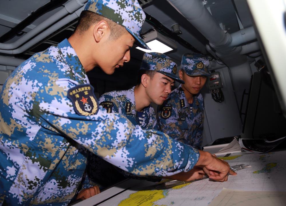 参演编队指挥组针对搜救方案,在海图上研究细节。曾行贱摄