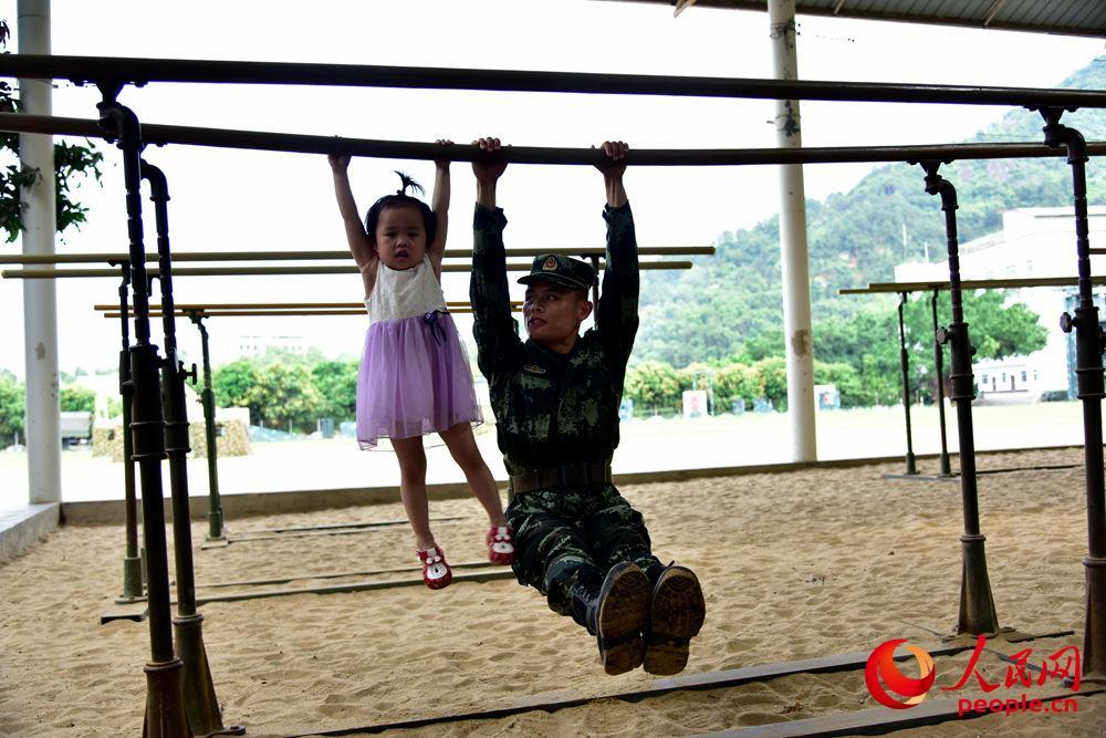 """图为军爸与孩子正在""""比拼""""力量"""