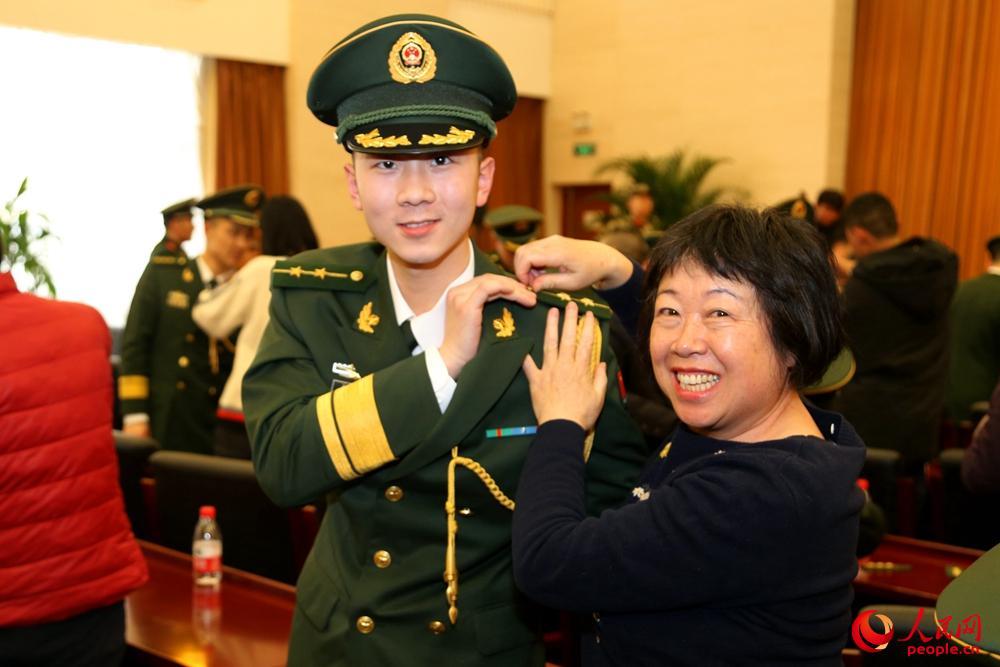 一位母亲为儿子佩戴警衔。姜润邈 摄