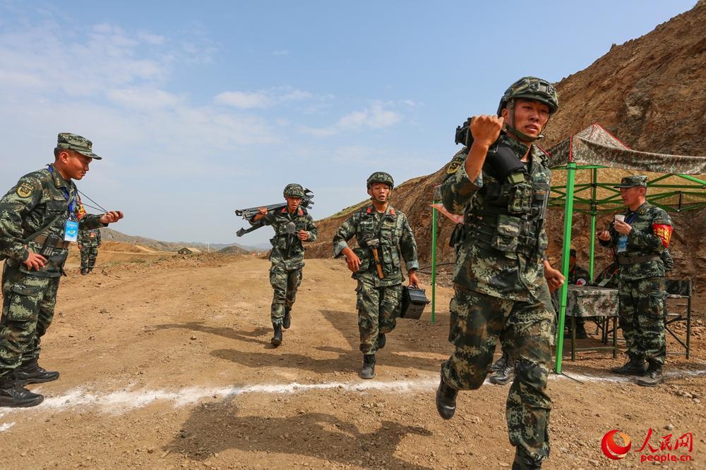 自动榴弹发射器战术射击中,比武队员携装奔袭2公里,向射击阵地前进。安晓惠摄