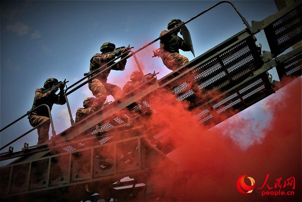 武警广西总队机动支队特战队员利用攀登突击车向目标发起突击。