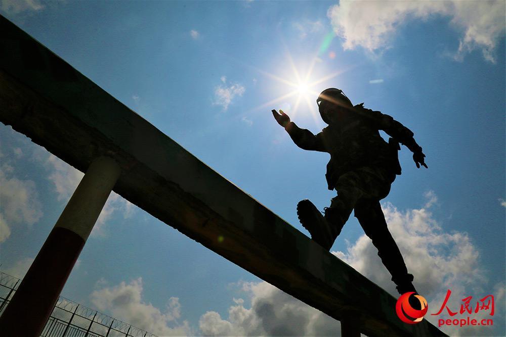 2019年4月24日,400米障碍训练中,一名武警官兵快速通过独木桥。
