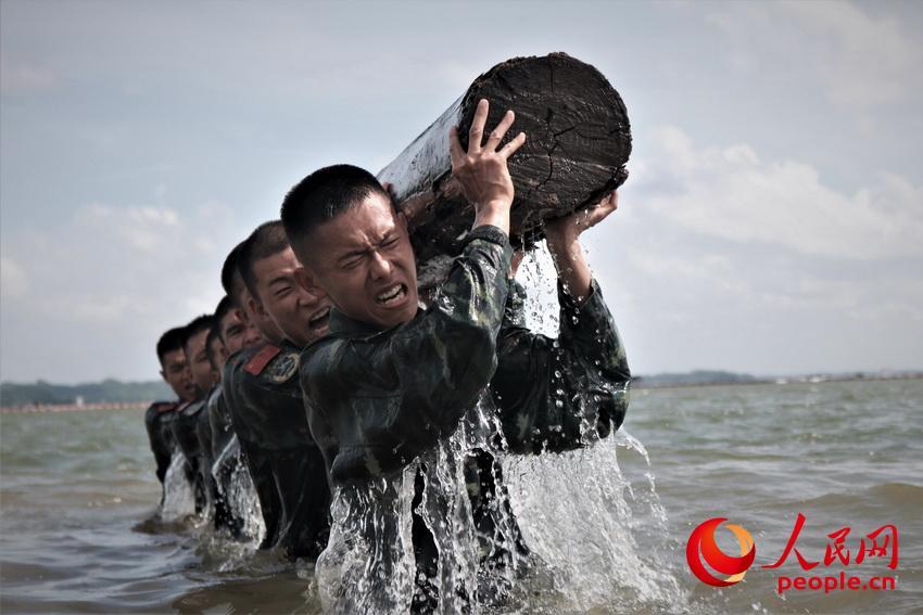 特战队员在海水中进行推举圆木训练