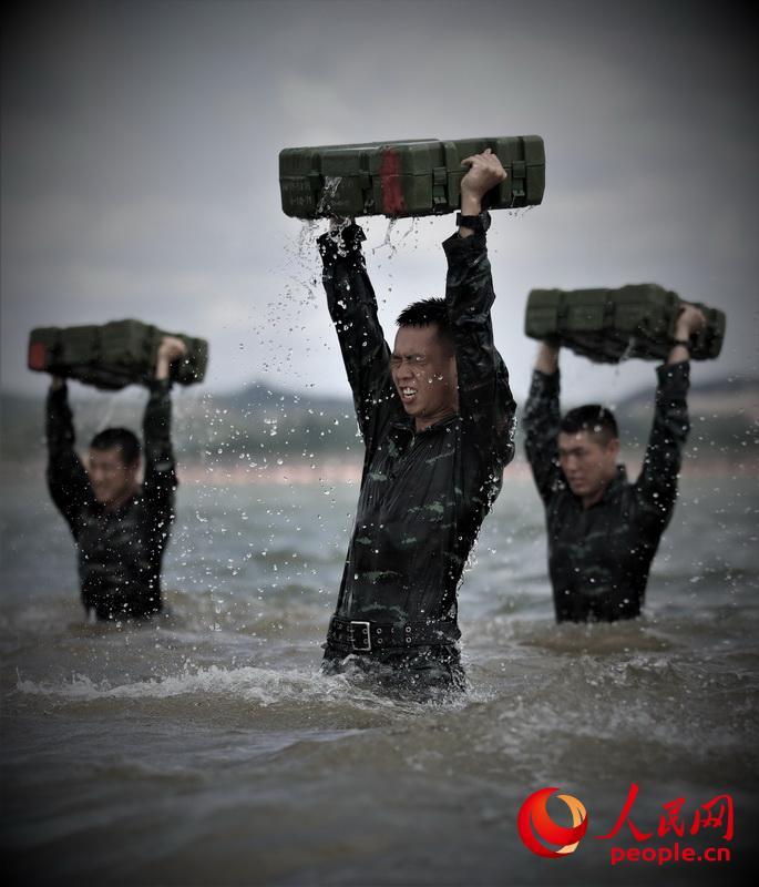 特战队员在海水中进行推举子弹箱训练