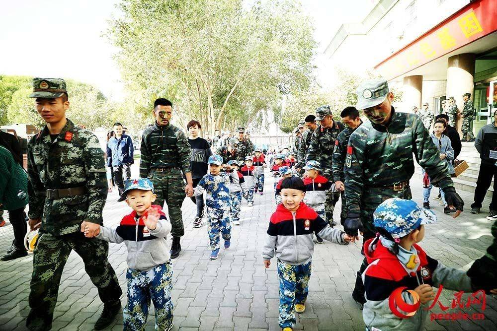 武警官兵拉着孩子们参观营区。