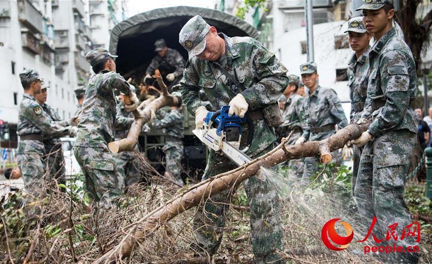 """驻澳门部队官兵帮助抗击""""天鸽""""台风灾害,清理被风吹倒的树木(2017年8月27日摄)。 (叶华敏 摄)"""