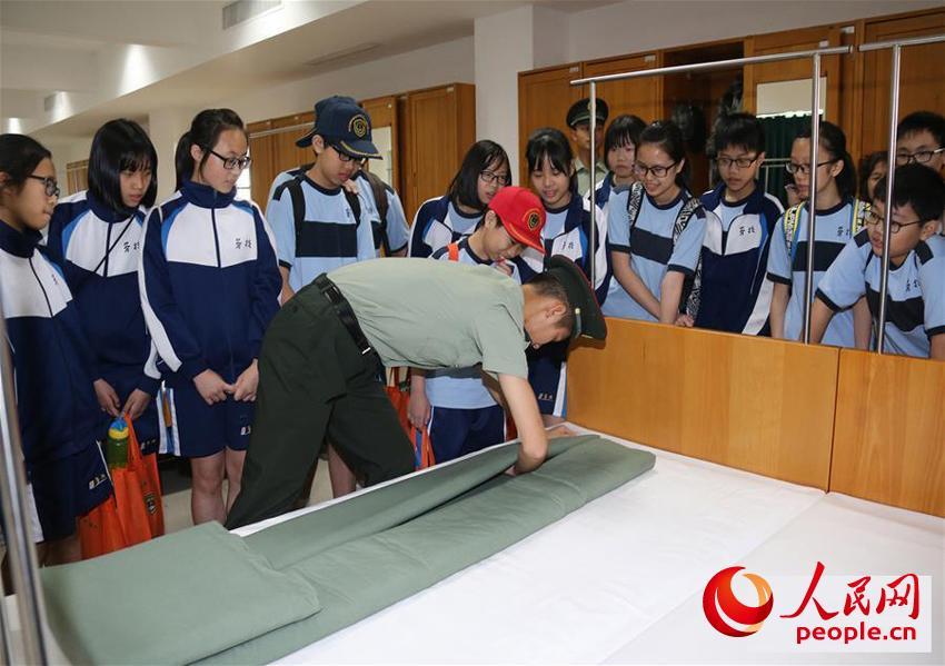 驻澳门部队在军营开放活动中邀请市民走进军营参观,战士们向小学生演示叠军被(2017年8月24日摄)。 (叶华敏 摄)