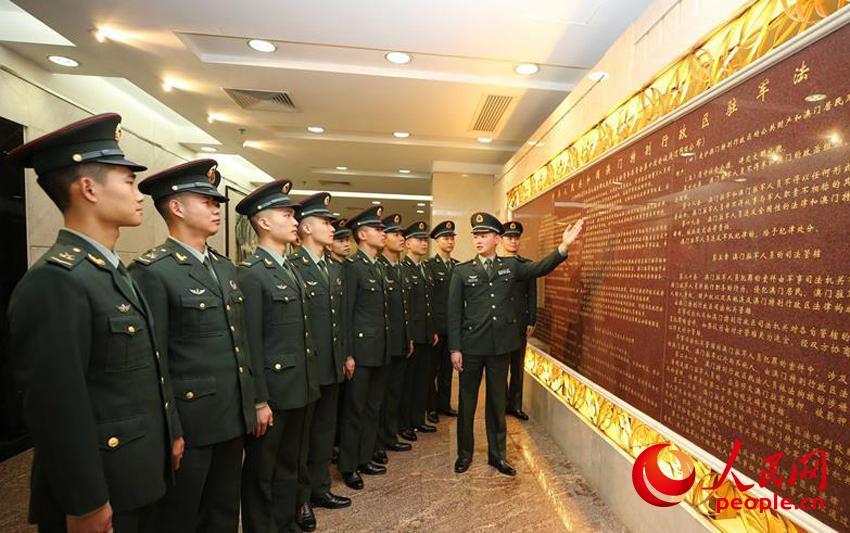 驻澳门部队组织官兵学习刻在新口岸大厦大厅墙上的驻军法(2019年12月2日摄)。(叶华敏 摄)