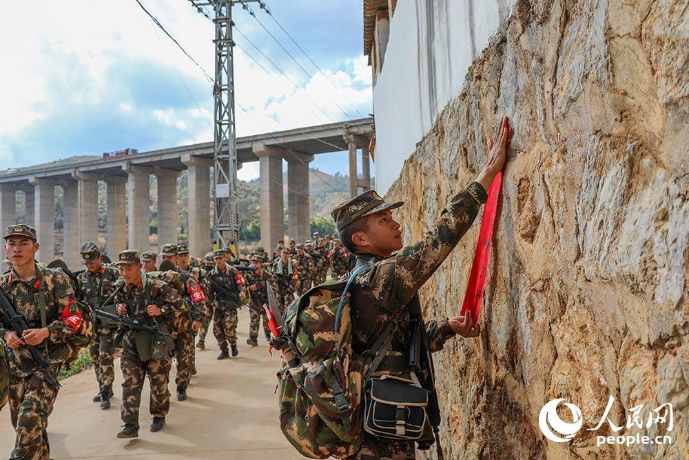 行军途中,官兵张贴宣传标语,做到走一路红一线。