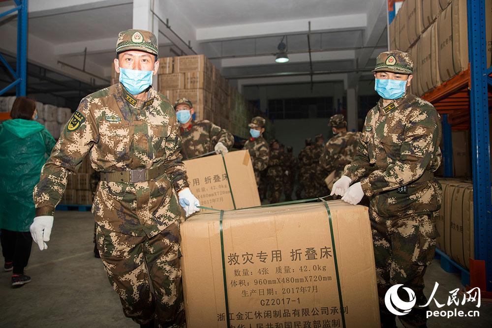 2月9日,武警官兵正在搬运救援物资。