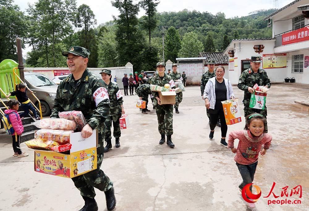 """队官兵给孩子们送去""""六一""""节礼物。"""