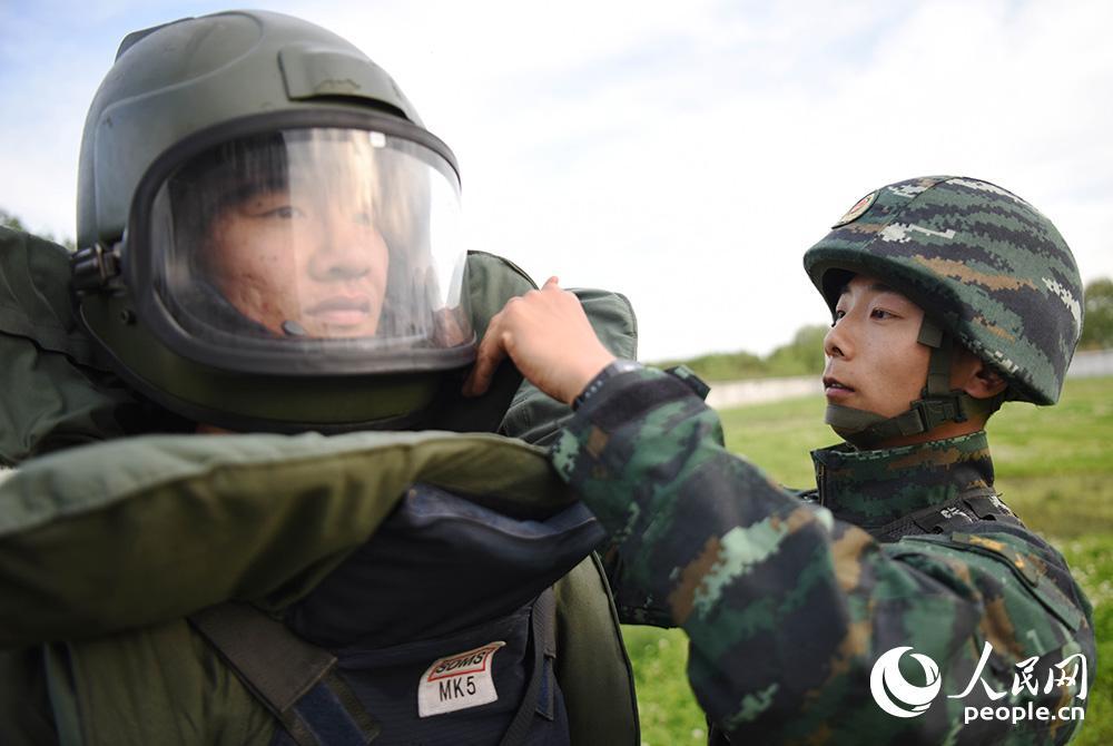 特戰小隊排爆副手劉昌運(右)在幫隊友姚文強穿排爆服。