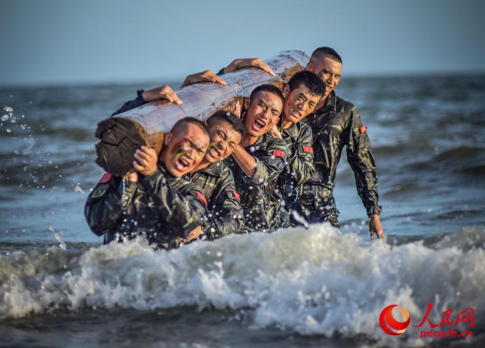 官兵进行海水中推举圆木训练。