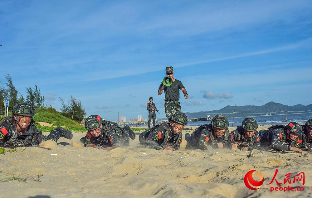 在沙滩上进行低姿匍匐训练。