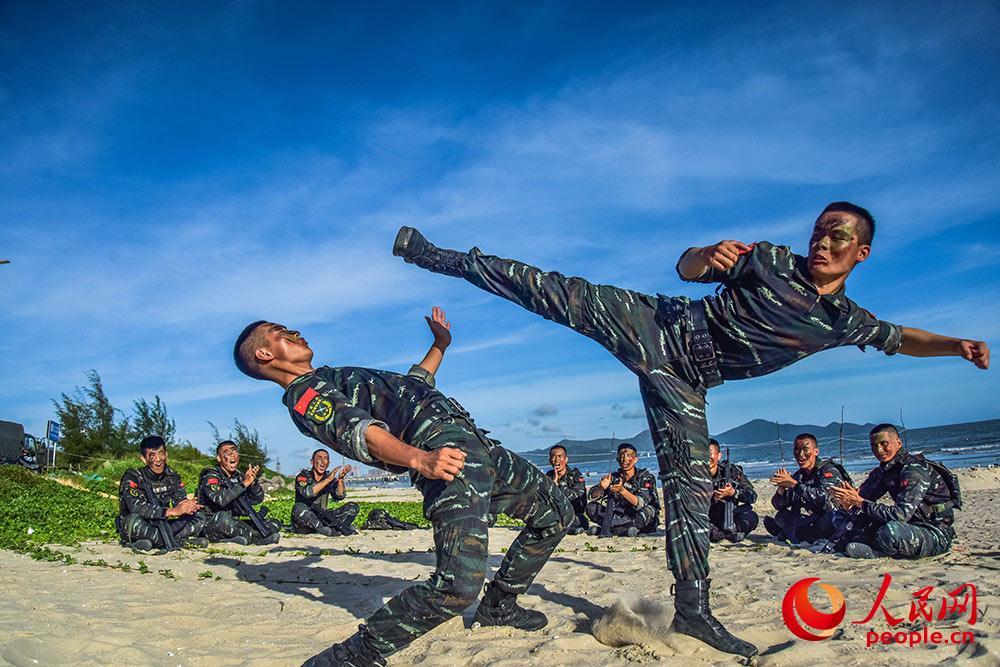 在沙滩上进行搏击对抗训练。