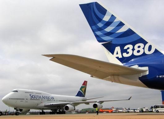 一架波音747飞机从抵达坦博国际机场的空中客车a380飞机附近滑过.