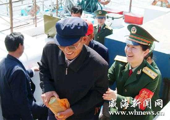 图为刘公岛边防派出所的女警官小心翼翼地搀扶老人登岸.