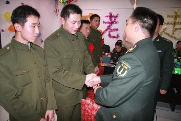 图为部队领导为退伍老兵发放纪念品.
