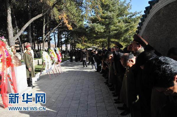 2010年11月25日,在朝鲜平安南道桧仓郡中国人民志愿军烈士陵园,参加祭奠的朝中两国人员向毛岸英烈士墓默哀致敬。 摄影:新华社记者  赵展